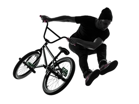 one caucasian man exercising bmx acrobatic figure in silhouette studio isolated on white background photo