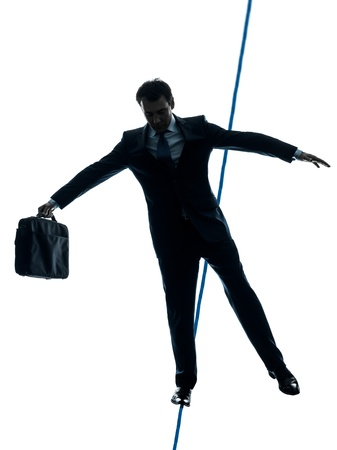 one caucasian Businessman  tightrope walker in silhouette studio isolated on white background Stock Photo - 17798154