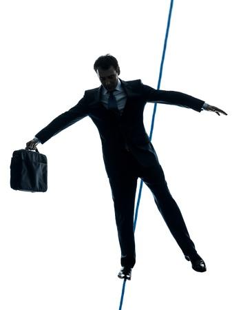 marcheur: une caucasien d'affaires funambule en studio silhouette isolé sur fond blanc
