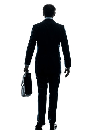 back shots: one caucasian businessman walking rear view in silhouette studio isolated on white background Stock Photo