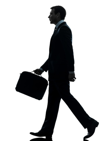 walk away: one caucasian businessman walking side view in silhouette studio isolated on white background