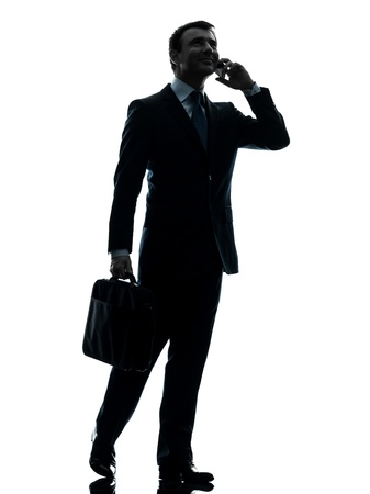 one caucasian businessman walking on the telephone in silhouette studio isolated on white background photo