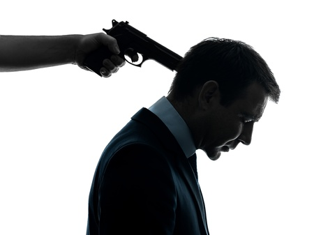 un uomo d'affari caucasico con pistola che punta alla testa in studio silhouette isolato su sfondo bianco