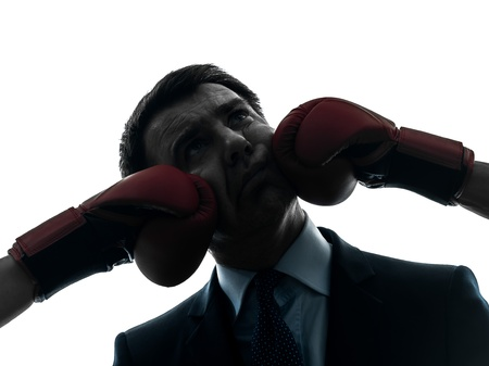 vanquish: one caucasian businessman punch by boxing gloves  in silhouette studio isolated on white background Stock Photo