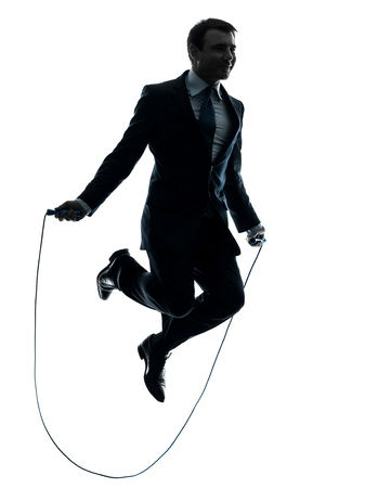 one caucasian businessman exercising jumping rope in silhouette studio isolated on white background photo