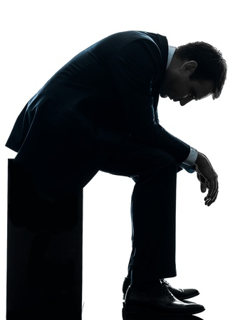 desperate: un hombre de negocios caucásico triste sentado pensativo mirando hacia abajo en el estudio de la silueta aislado en el fondo blanco Foto de archivo