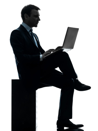 one caucasian businessman computing laptop computer  in silhouette studio isolated on white background photo