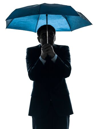 one caucasian anxious business man under umbrella  in silhouette studio isolated on white background photo