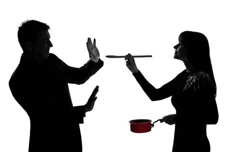 one caucasian couple man and woman tasting cooking sauce pan in studio silhouette isolated on white background Stock Photo - 17798115