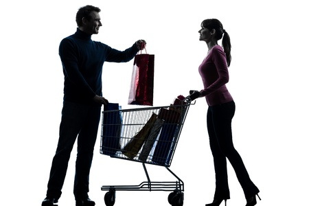 one caucasian couple woman man with shopping cart  and gifts in silhouette studio isolated on white background photo