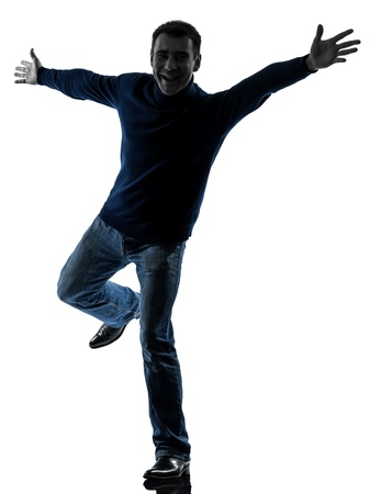 arms  outstretched: one caucasian man happy saluting  full length in silhouette studio isolated on white background Stock Photo