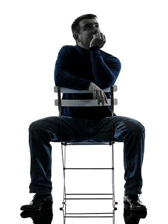 one caucasian man sitting  thinking pensive  full length in silhouette studio isolated on white background Stock Photo - 17798276
