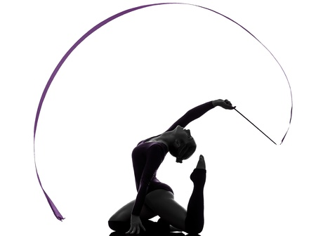 rhythmic gymnastics: una mujer caucásica ejercicio de gimnasia rítmica con la cinta en el estudio de silueta aislados sobre fondo blanco