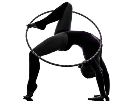 one caucasian woman exercising Rhythmic Gymnastics jumping hoop  in silhouette studio isolated on white background photo