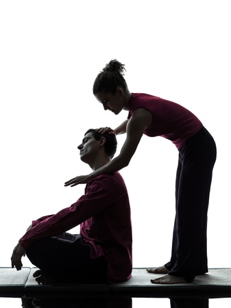 shiatsu: one man and woman perfoming thai massage in silhouette studio on white background