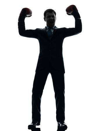 one caucasian businessman with boxing gloves   in silhouette studio isolated on white background photo