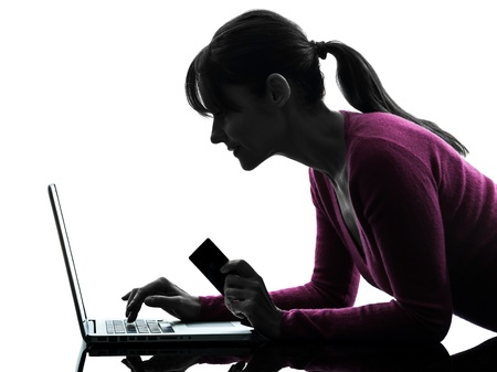 one caucasian woman holding credit card  computing laptop computer  in silhouette studio isolated on white background Stock Photo - 18238053
