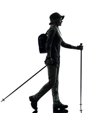 trekker: one caucasian woman trekker trekking walking in silhouette studio isolated on white background