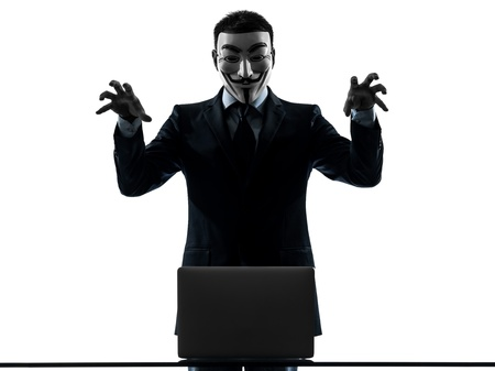 PARIS– OCTOBER 30 : one man dressed and masked as a  member of Anonymous underground group member computing computer menacing on October 30, 2012 in Paris ,France