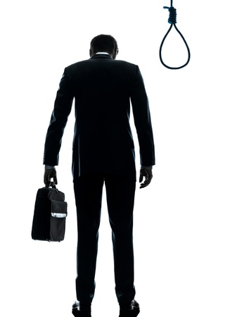 man looking out: one caucasian business man  rear view standing in front of hangmans noose in silhouette studio isolated on white background Stock Photo