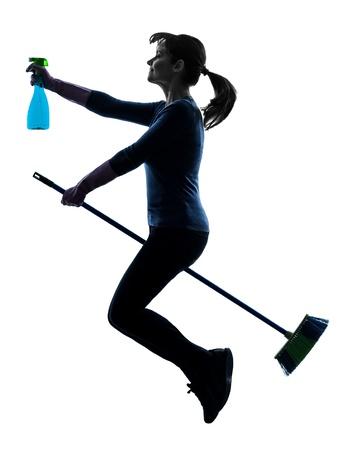 escoba: una mujer cauc�sica de limpieza de polvo de limpieza escoba voladora en el estudio de la silueta aislado en el fondo blanco Foto de archivo
