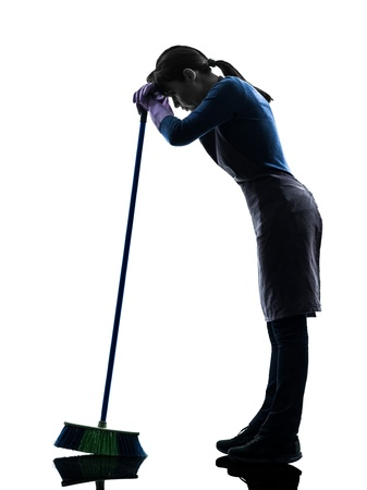 brooming: one caucasian woman maid cleaning tired brooming   in silhouette studio isolated on white background
