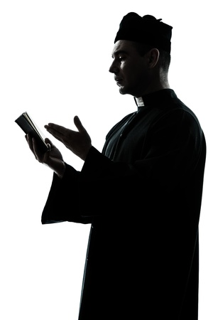 bishop: one caucasian man priest reading bible silhouette in studio isolated on white background