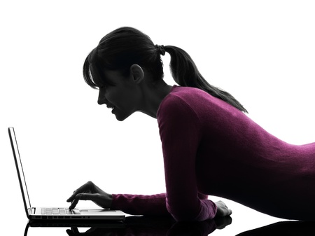 one caucasian woman computing laptop computer  in silhouette studio isolated on white background Stock Photo - 18353521