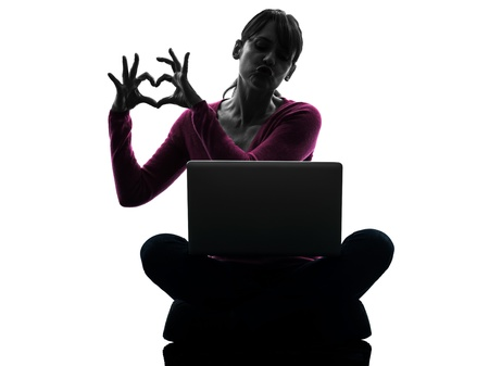 one caucasian woman heart gesture computing laptop computer  in silhouette studio isolated on white background Stock Photo - 18353489