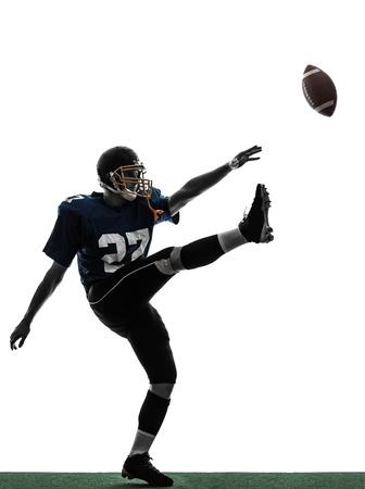 uniforme de futbol: un pateador de fútbol americano caucásico hombre jugador pateando en el estudio de la silueta aislado en el fondo blanco