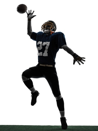 american football player: one caucasian american football player man catching receiving in silhouette studio isolated on white background