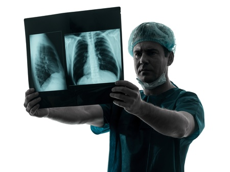 one caucasian man doctor surgeon radiologist medical examaning lung torso  x-ray image silhouette isolated on white background Stock Photo - 18518224