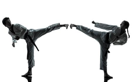 girl kick: one couple man woman couple exercising karate taekwondo martial arts in silhouette studio isolated on white background