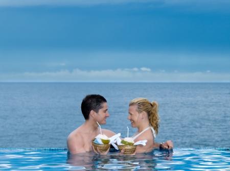 honeymooners: hermoso cauc�sico disfrutando de sus vacaciones en una piscina junto al mar bebiendo leche de coco