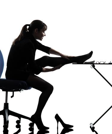 secretary desk: one caucasian business woman massaging her leg  in silhouette studio isolated on white background