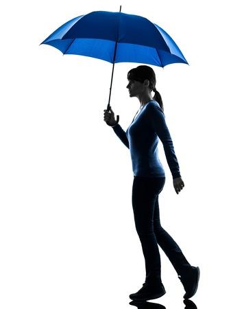 woman umbrella: one caucasian woman holding umbrella  in silhouette studio isolated on white background