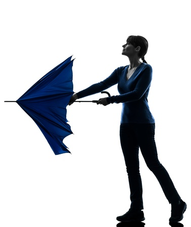 profile: one caucasian woman opening closing umbrella  in silhouette studio isolated on white background