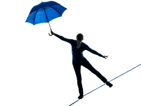 one caucasian woman holding umbrella  in silhouette studio isolated on white background photo