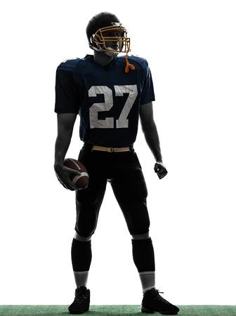 the football player: un hombre cauc�sico quarterback americano jugador de f�tbol de pie en el estudio de la silueta aislado en el fondo blanco