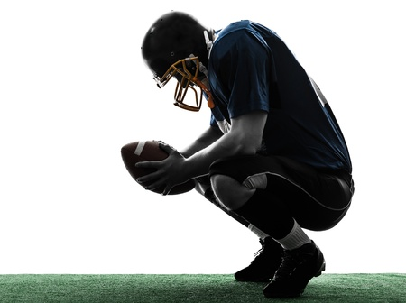 fuball spieler: ein caucasian besiegt american football player Mann in Silhouette Studio isoliert auf wei�em Hintergrund