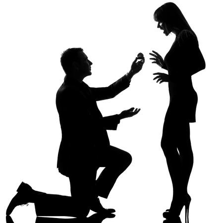 siluetas de enamorados: un hombre caucásico de rodillas anillo de compromiso y ofrenda feliz mujer sorprendida en estudio, silueta, aislado sobre fondo blanco