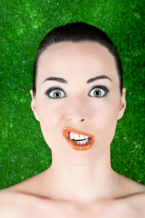 grimacing: Closeup portrait of a woman funny grimacing  isolated on green Stock Photo