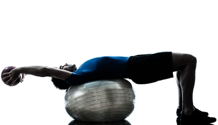 lying on side: one caucasian man exercising workout fitness ball in silhouette studio  isolated on white background