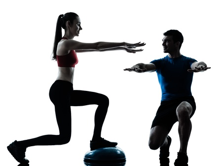 personal trainer: personal trainer man coach and woman exercising squats on bosu silhouette  studio isolated on white background Stock Photo