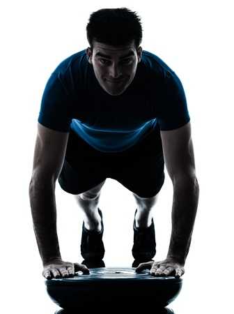 pushups: one caucasian man exercising push ups on bosu workout fitness in silhouette studio  isolated on white background Stock Photo