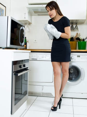 imploring: beautiful caucasian woman in a kitchen waiting with anxiety in front of the oven