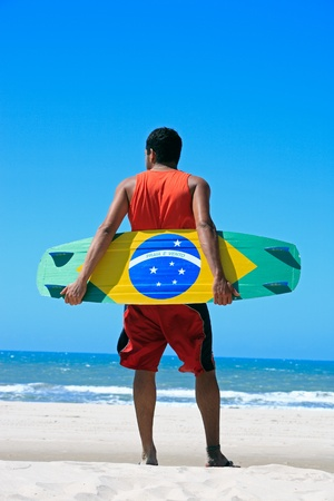 Kite surfer with the brazilian flag painted on the board with praia e vento (beach and wind) instead of ordem e progresso  in prainha beach near fortaleza photo