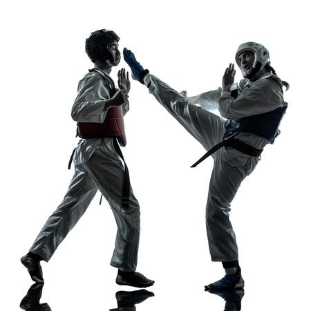 taekwondo: one couple man woman couple exercising karate taekwondo martial arts in silhouette studio isolated on white background