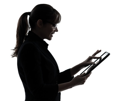 business woman standing: one caucasian business woman computer computing typing digital tablet in silhouette studio isolated on white background