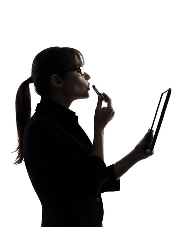 one caucasian business woman  computer computing digital tablet applying lipstick  in silhouette studio isolated on white background photo